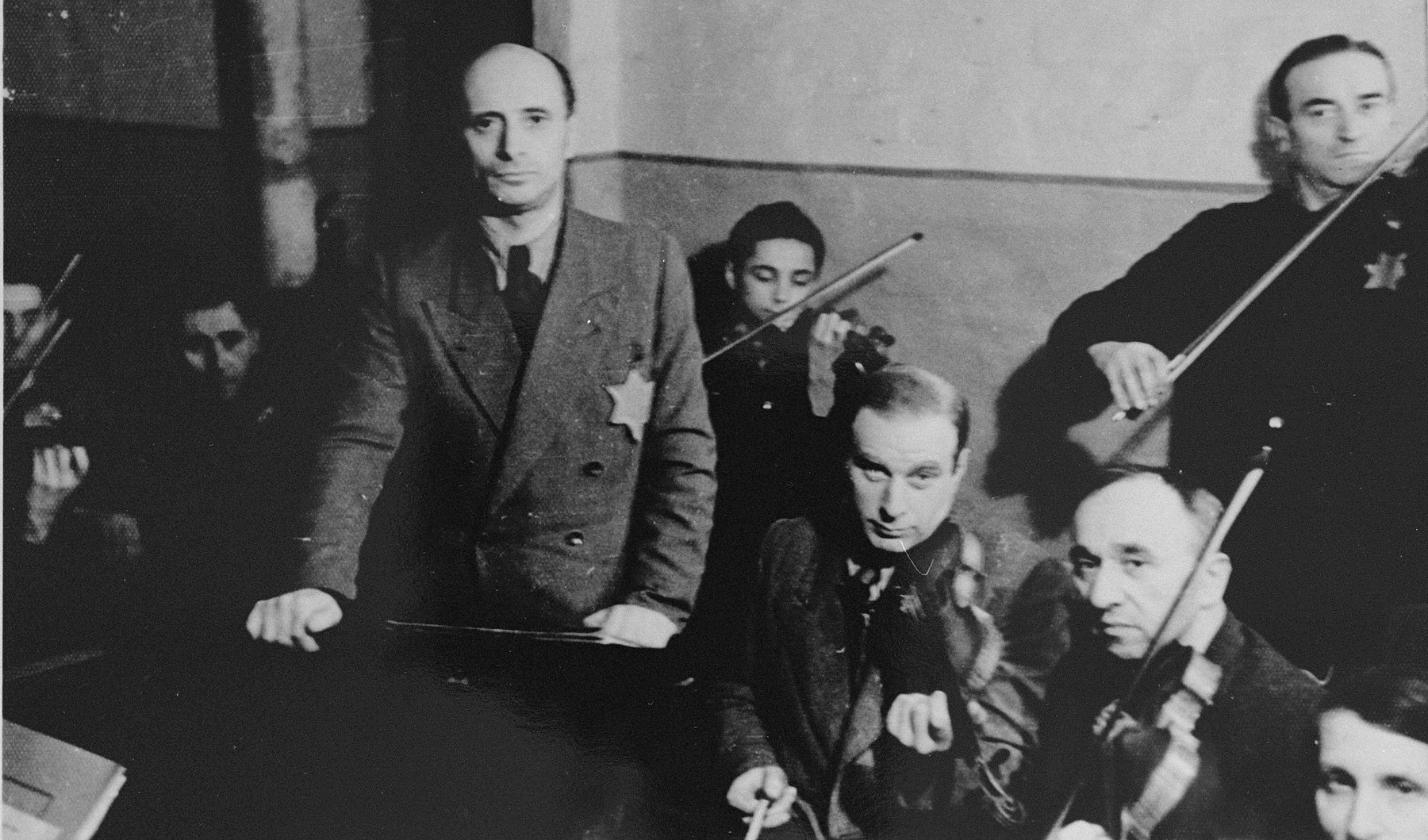 Performance of the Kovno ghetto orchestra.   Among those pictured are: Yankele (the 13-year-old youth playing the violin at the back), Michael Hofmekler (standing at the left), Boris Stupel (sitting next to Hofmekler), Alexander (Shmaya) Stupel (standing at the top right).  Boris Stupel survived Dachau and later immigrated to Australia.  His brother, Alexander, perished in Dachau.