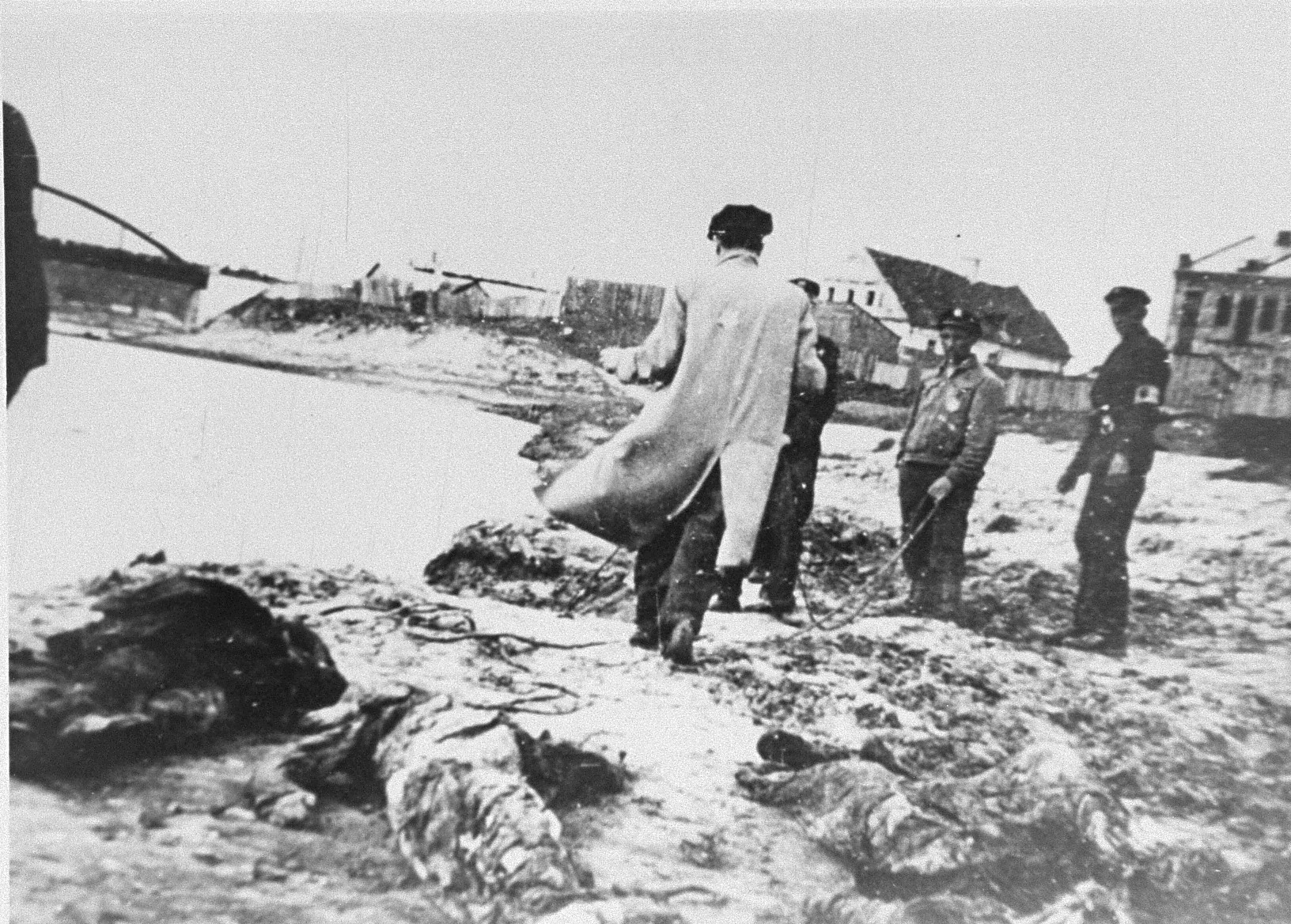 Members of the Kovno ghetto fire brigade pull the bodies of murdered Jews from the Viliya (Neris) River.