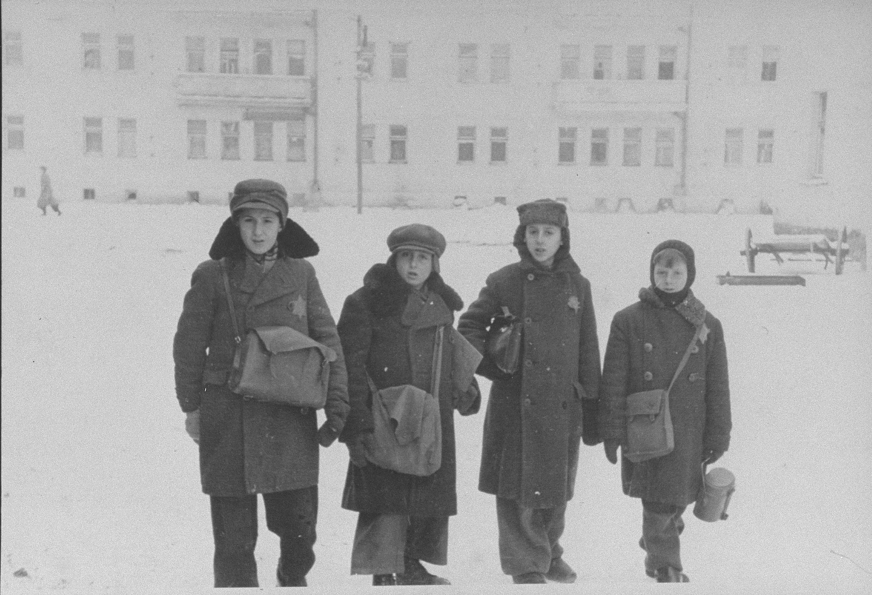 Four school boys pose on a snowy street in the Kovno ghetto with their school bags.  Pictured on the far right is Isroel Isser Shlapoberski (Murka).  According to Rabbi Ephraim Oshry, the boys are students in the religious Tifferes Bachurim school.