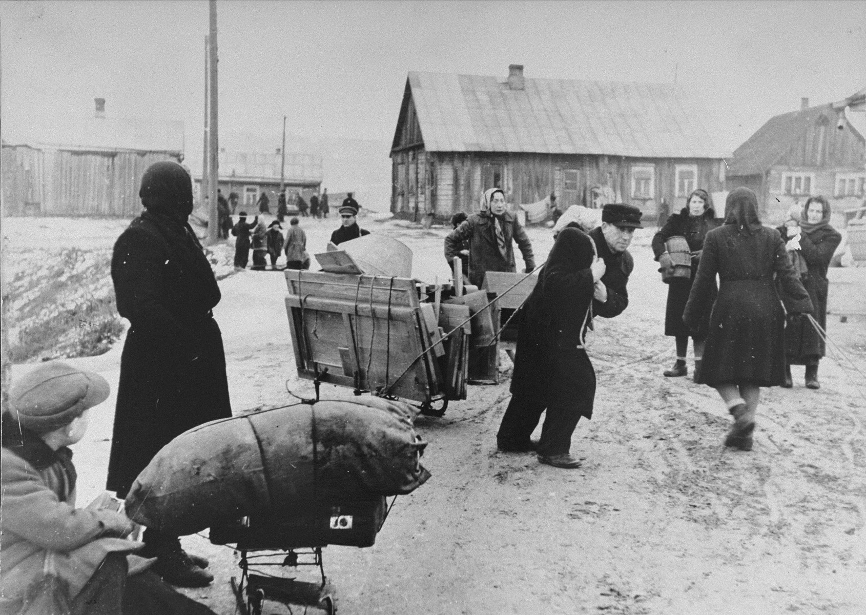 Jews move their belongings into the Kovno ghetto.  The man pulling the disassembled wardrobe is George Kadish's brother-in-law.  He never put it together because there was not enough space in his new quarters. Clothes were hung from nails (made out of barbed wire) in the wall.
