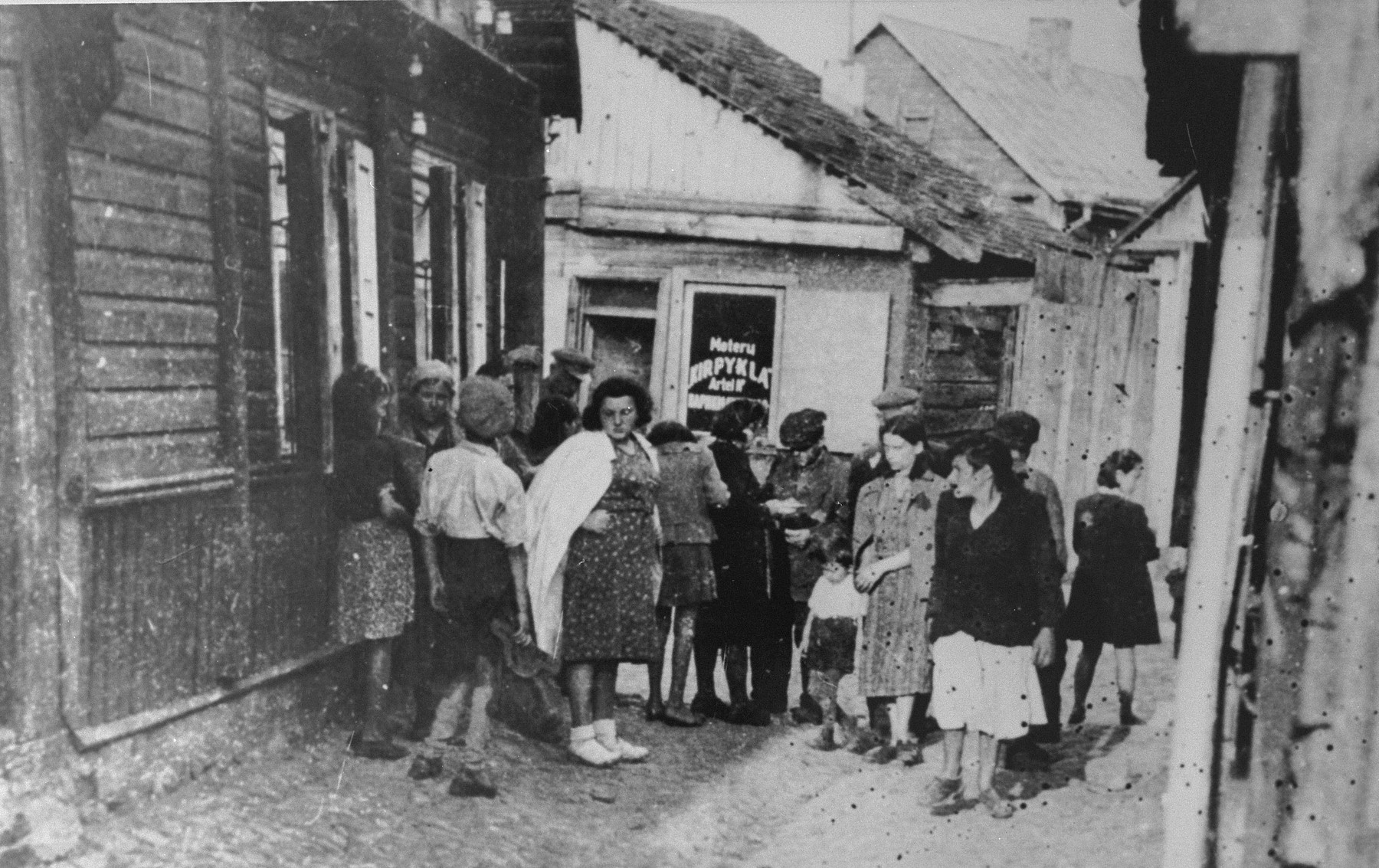 A group of Jewish women converse in an alley outside the only barbershop in the Kovno ghetto.