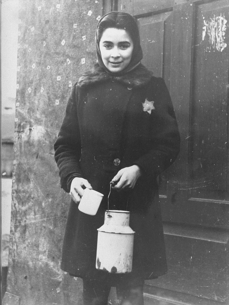 Portrait of a young girl holding a milk can in the Kovno ghetto.   Pictured is Helen Verblunsky, who is delivering milk to one of her mother's customers, a gynecologist named Dr. Nabriskin.