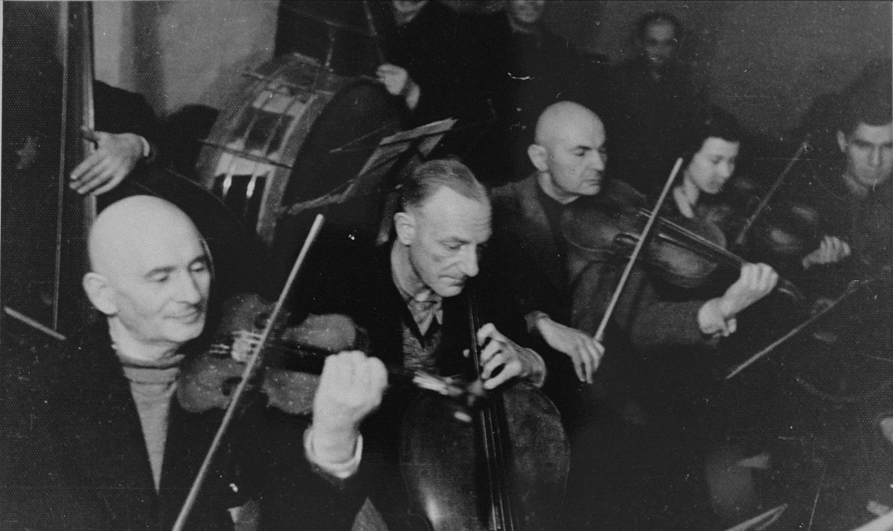 Performance of the Kovno ghetto orchestra.    Among those pictured are: Mordechai Borstein (left), Korijski (middle), and Maya Gladstein (right).  Bornstein and Gladstein both survived and moved to Israel, while Korijski perished.