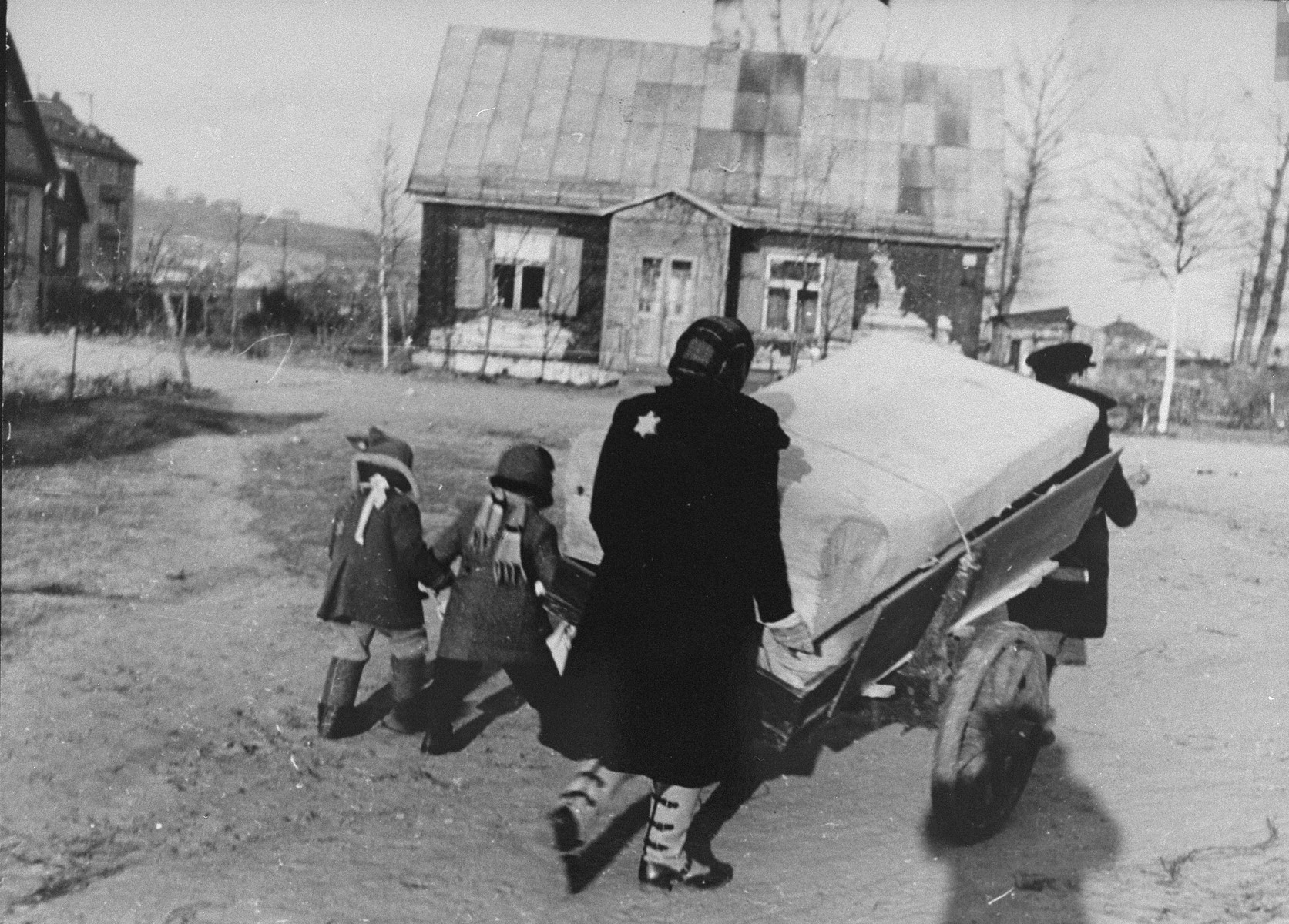 A woman pushes a cart piled with household belongings through the streets of the Kovno ghetto.  The shadow of the photographer George Kadish can be seen in the lower right hand corner.