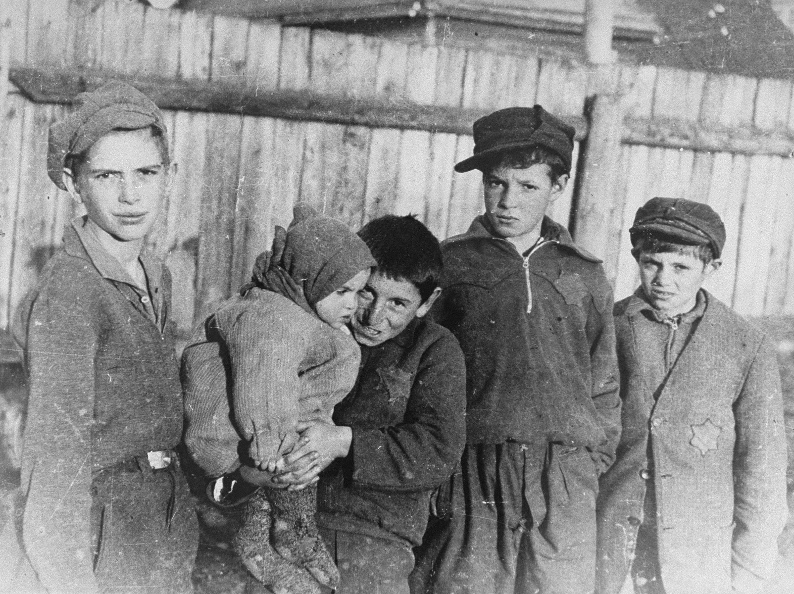 A group of young boys holding a small child in the Kovno ghetto.