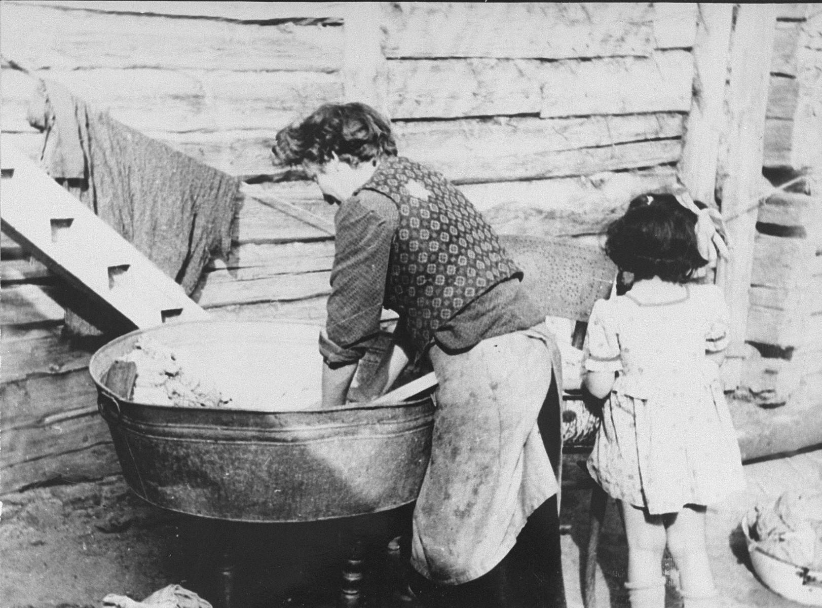 A woman does the washing in a basin outside at the ghetto laundry in the Kovno ghetto.  The laundry, which began operation on February 16, 1942, was one of 44 workshops in the ghetto.  It employed 41 persons, mostly women.  The laundry was very difficult to outfit initially since the ghetto had no sewer system or water mains, but ghetto engineers installed heating and water pipes to make it fully operational.  The laundry cleaned clothing and linens of German civil administrators, military and police.   In addition to providing labor for women who would have found it physically or personally difficult to join brigades outside of the ghetto, the laundry provided another benefit as well.  The ghetto was not allocated a soap ration.  Therefore, during the summer months, workers at the laundry frequently threw linen straight into the river for easy cleaning and channeled the saved soap to ghetto inhabitants.