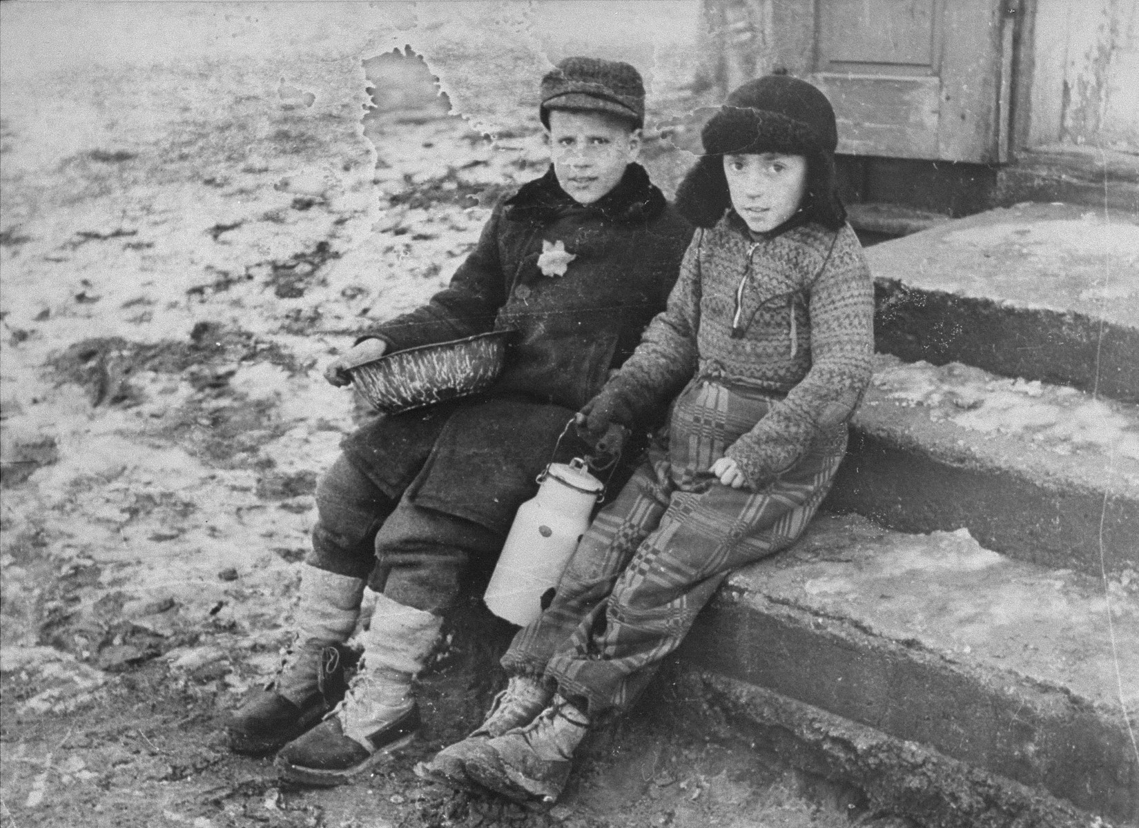 """Portrait of two young boys with a milk can.  The caption by George Kadishon the back of the photo reads """"Winter in the Kovno ghetto.  Early in the morning in line for soup""""."""
