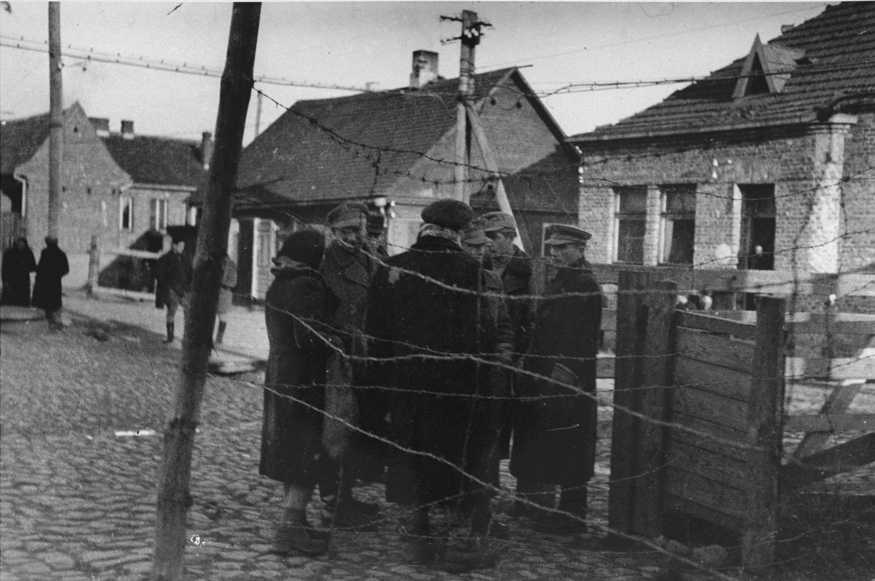 "Jacob (Yankel) Verbovski (far right), a representative of the Altestenrat labor office, talks with a group of Jews near the Varniu Street entrance to the Kovno ghetto.  Verbovski was known as the ghetto's ""count man"".  He was in charge of counting people coming and going into the ghetto.  In that capacity he helped members of the resistance to escape from the ghetto, and he helped smuggle weapons and other illegal goods into the ghetto.  Verbovski survived the war and immigrated to the United States."
