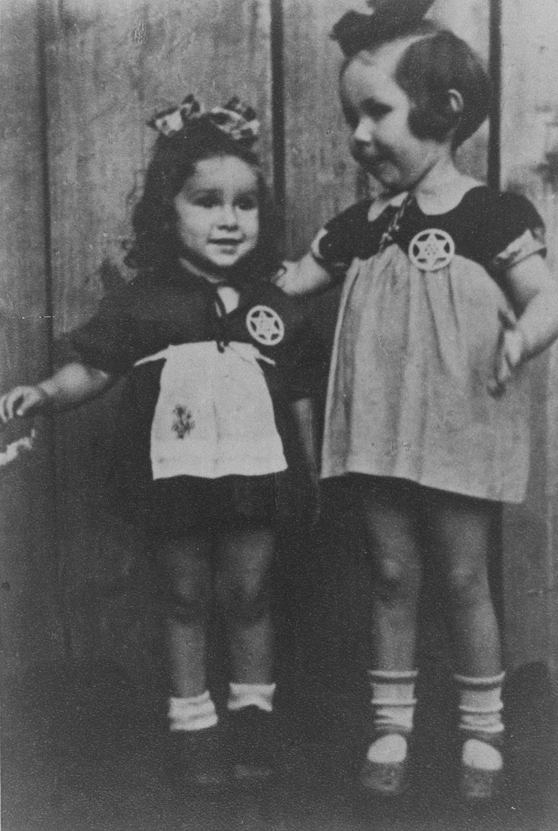Two young girls in the Kovno ghetto wearing Stars of David that were fashioned out of wood by their uncle.  Pictured are Henia Wisgardisky (right) and her cousin, Bluma Berk. This photograph was taken a few months before Henia's mother smuggled the two girls out of the ghetto.  Both children were hidden by Lithuanian families and survived the war.