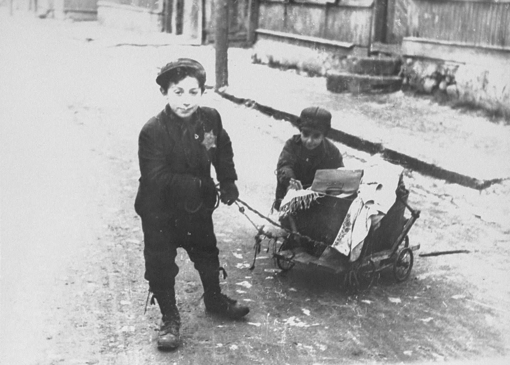"""Two young boys pull and push a wagon in the Kovno ghetto.   According to Solly Ganor: """"Two orphans whose parents were murdered in the beginning of the war. There were many children like them in the ghetto. They lived with a sick grandmother in half a room sharing with other two families. He was the provider of the family, trading, stealing and begging. I would see him at the corner """"market"""" place, trying to sell old shoes, torn garments and old books. He, his little brother and his grandmother were murdered at the """"Children's Action"""". """""""
