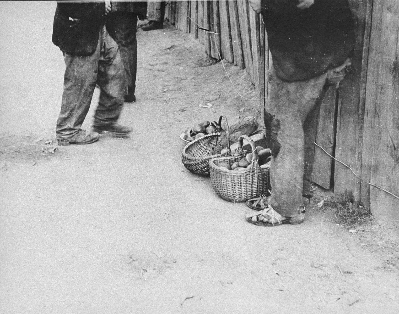 The feet of two men who are standing on a street in the Kovno Ghetto.  The man at the right stands beside baskets of bread wearing sandals held together by string.