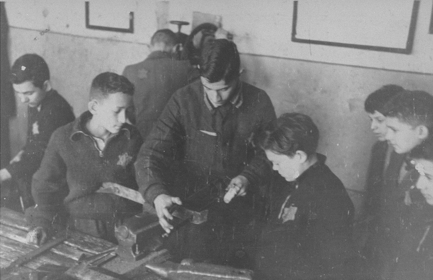 Children working in an ORT carpentry workshop in the Kovno ghetto.    Among those pictured are Eli Gotz (the older youth in the center) and Yizhak Koplowicz (the younger child next to him at the right).