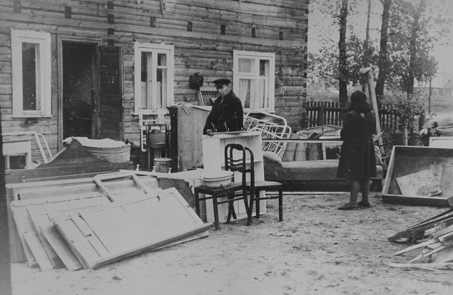 A Jew stands among disassembled furniture outside a house in the Kovno ghetto.