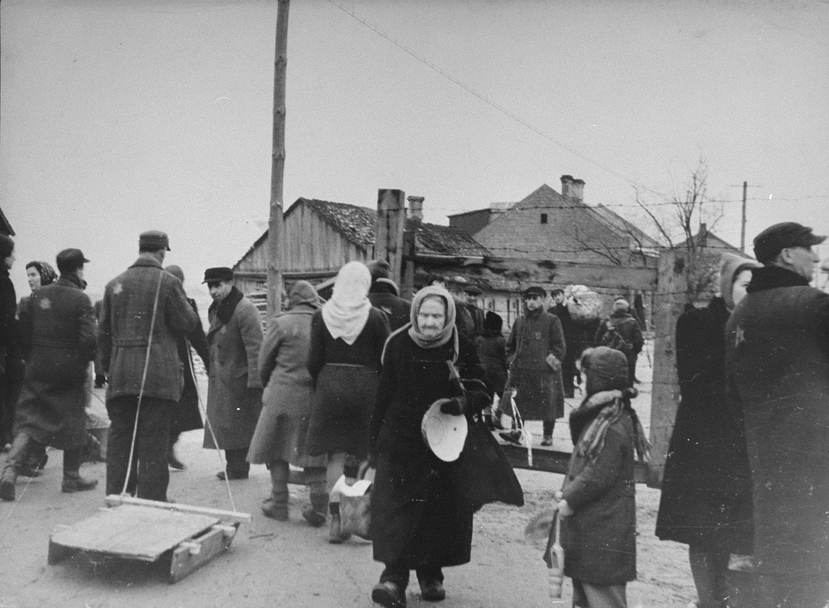 Jews move their household belongings to new quarters in the Kovno ghetto following a reduction in the size of the ghetto.  Among those pictured is Yitzhak Elhanan Rabinowich (far right), Jewish manager of the German labor office in the ghetto.  The elderly woman in the center is Sara Abramowitz.