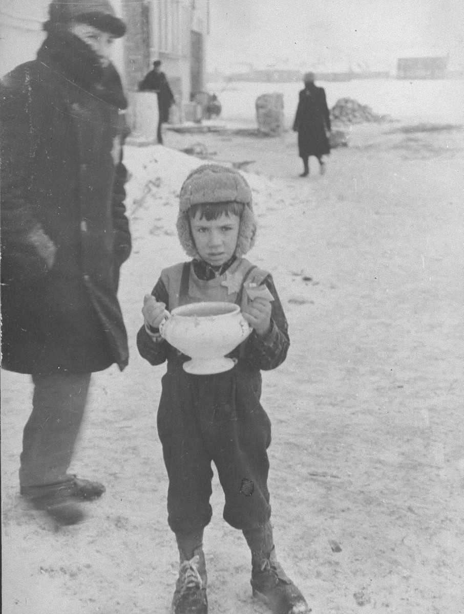 "A young boy in the Kovno Ghetto carrying a bowl of soup and holding food ration tickets.  According to Solly Ganor ""A five-year-old boy receives hot soup for the family from the ghetto soup kitchen. His father was murdered in the beginning of the war and the mother had to take care for the smaller children. The boy became the provider of the family. I saw him often standing at the corner trying to sell what was left of the family possessions. He was shot trying to escape from the Germans during the ""Children's Action"" on March 27, 1944. """