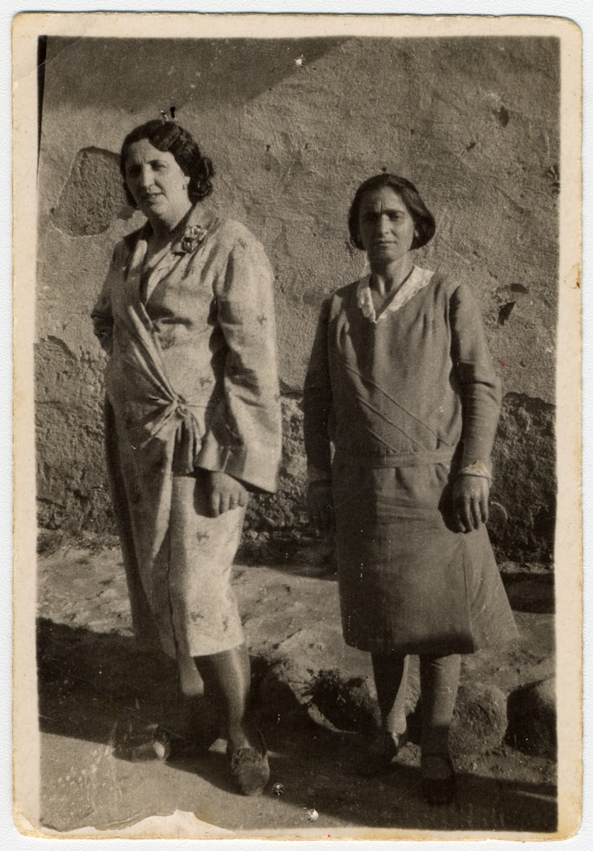 Two Macedonian Jewish friends pose for a photograph in the courtyard.    Pictured (left to right) are Elena Nale and Esterina Kolonomos (nee) Fransez.   Elena was a neighbor  and dressmaker who assisted the Kolonomos family during the Bulgarian occupation.