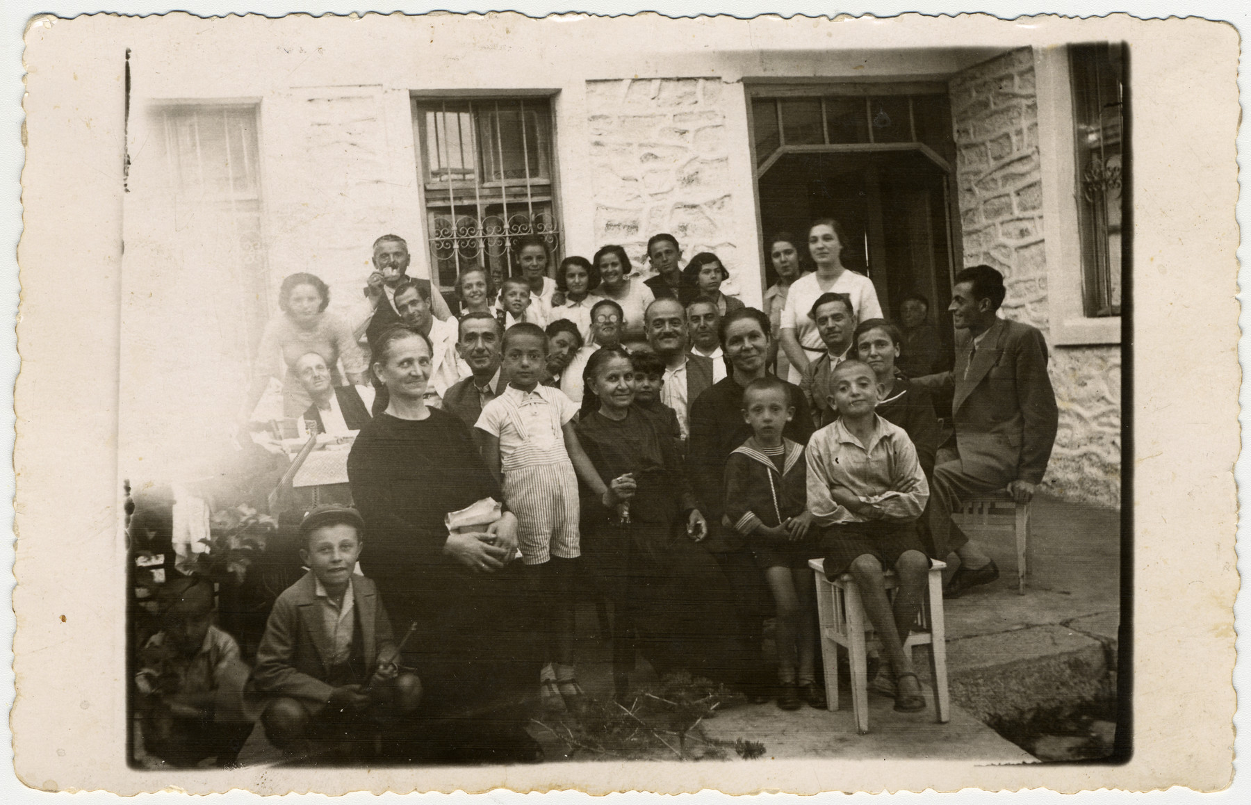 Two Macedonian families vacation together.  Among those pictured are Estarina, Bela, Jamila, Kalef, Menachem, and Rachel Kolonomos (center), at the country house of their neighbors Teliko and  Antigona Tahula.
