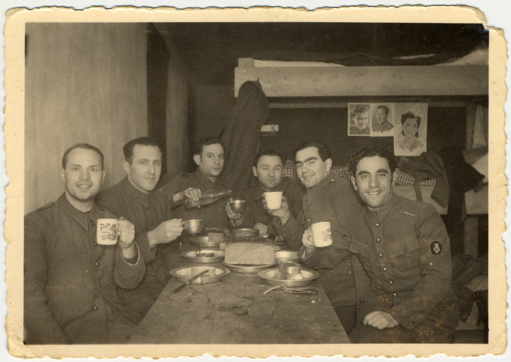 Jewish POWs eat potato pancakes in celebration of Hannuka inside their barracks in POW camp Stalag VIII.  Max Beker is pictured in the right, front.  Also pictured are Sokoloff, Philip, Kremin, Kopelansky and Katz.