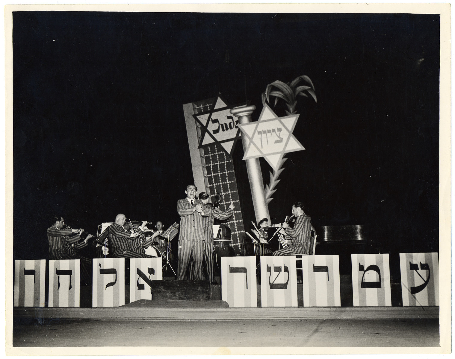 "The Saint Ottilien Ex-Concentration Camp Orchestra performs a concert in Munich for American soldiers and UJA staff.  The sign in front reads ""Am Yisrael Chai"" (the nation of Israel lives).    Pictured from left to right are Max Beker (violin), Max Borstein (violin), Melech Granat (drums), Jerzy Richter (voice), Fania Beker (piano) and Rala Wolfberg (clarinet).  See photograph 29734  for alternate caption."