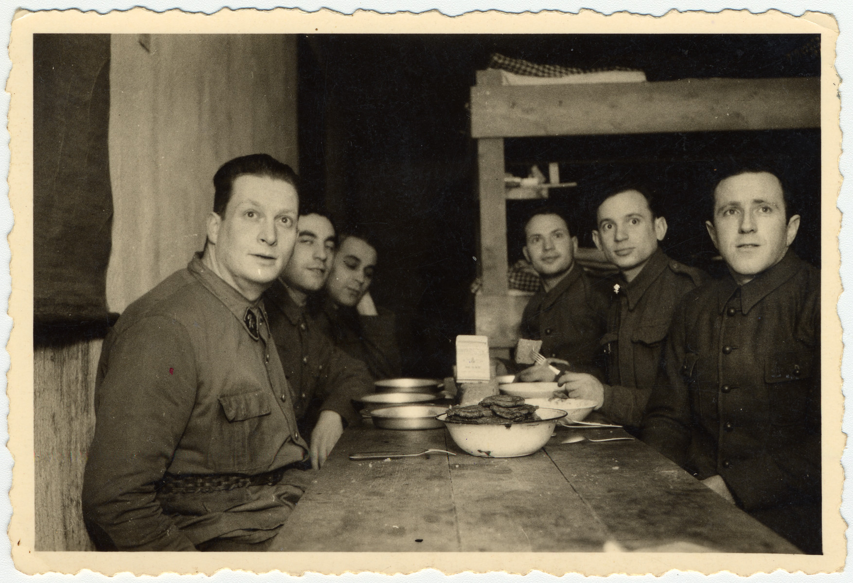 Polish prisoners-of-war celebrate Channukah in their barracks with potato pancakes.  Pictured from left to right are Sokoloff, Max Beker and Philip Kopolansky.
