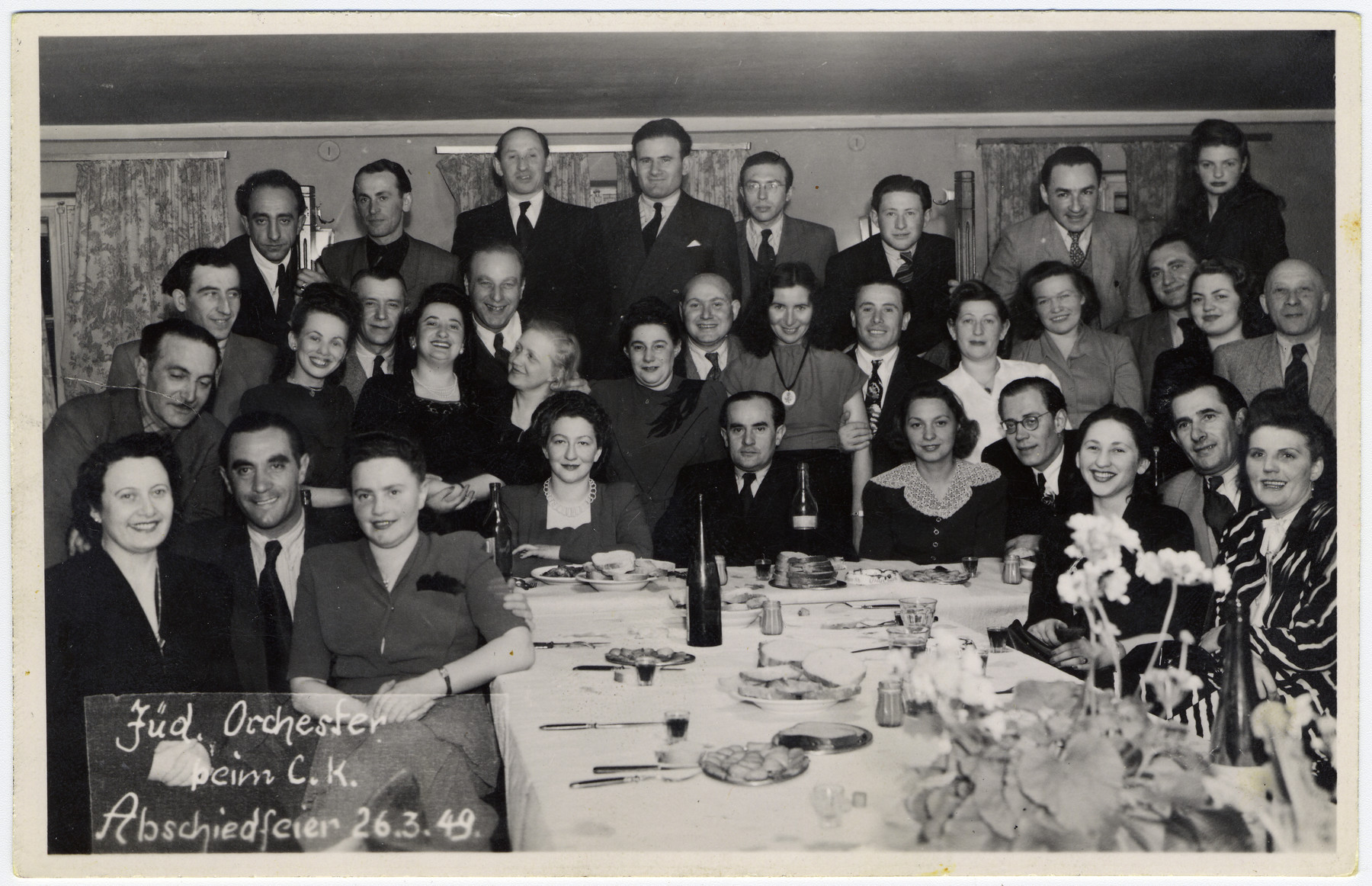 Members of the Jewish orchestra celebrate with friends at a farewell dinner.