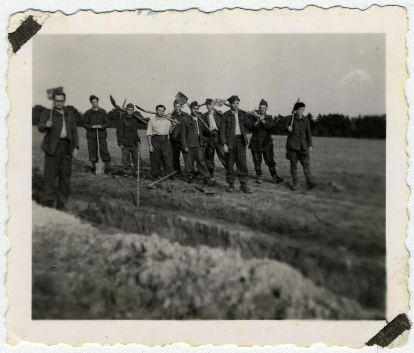Jewish prisoners-of-war pose with shovels while doing forced labor in an Arbeitskommando.