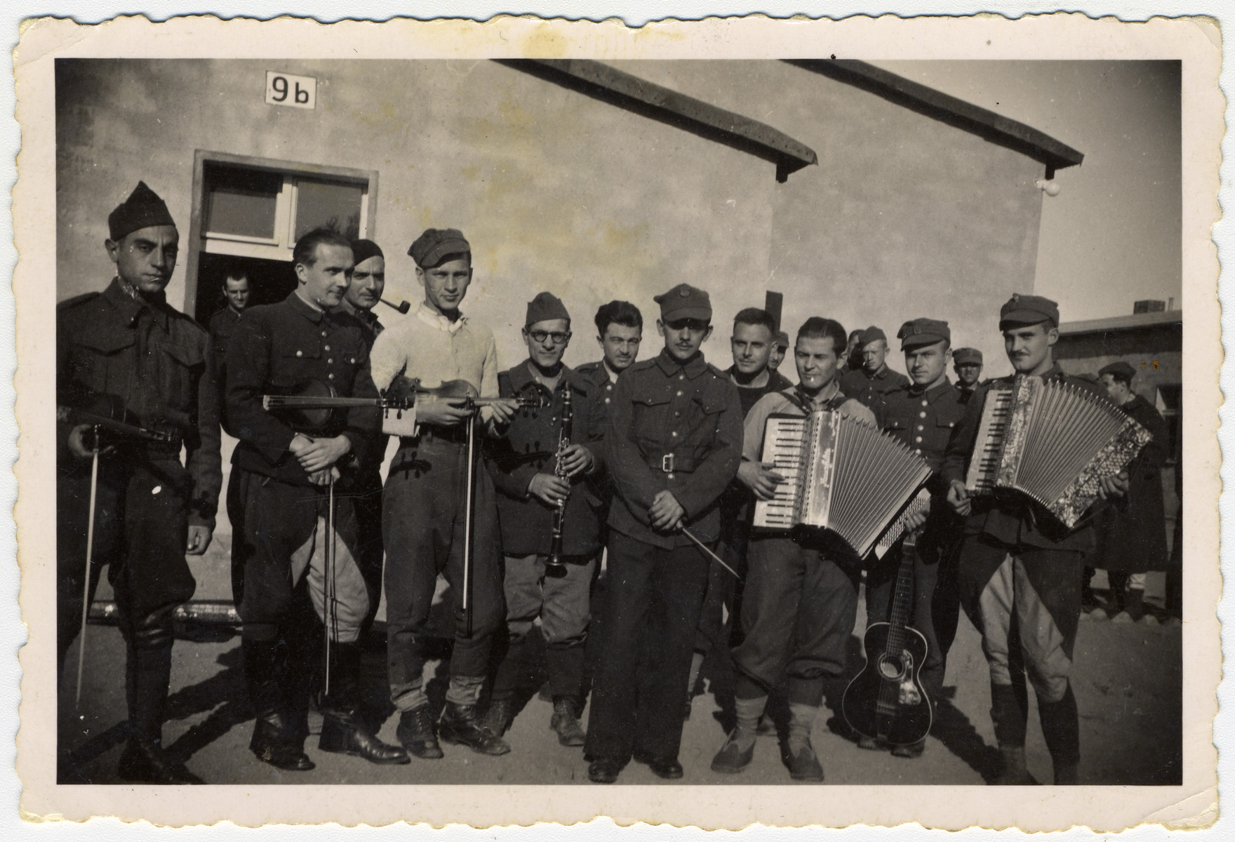 Group portrait of Polish prisoners-of-war holding musical instruments.  Max Beker is pictured on the far left with his violin.  This photograph was taken shortly after he was taken captive and after one of his first meetings with other prisoner muscians.