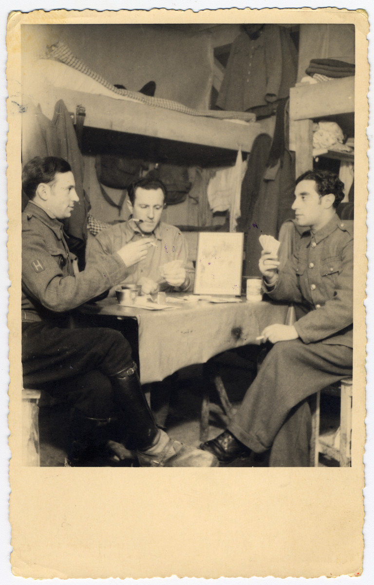 Jewish POWs play cards inside their barracks.  Max Beker is pictured on the right.