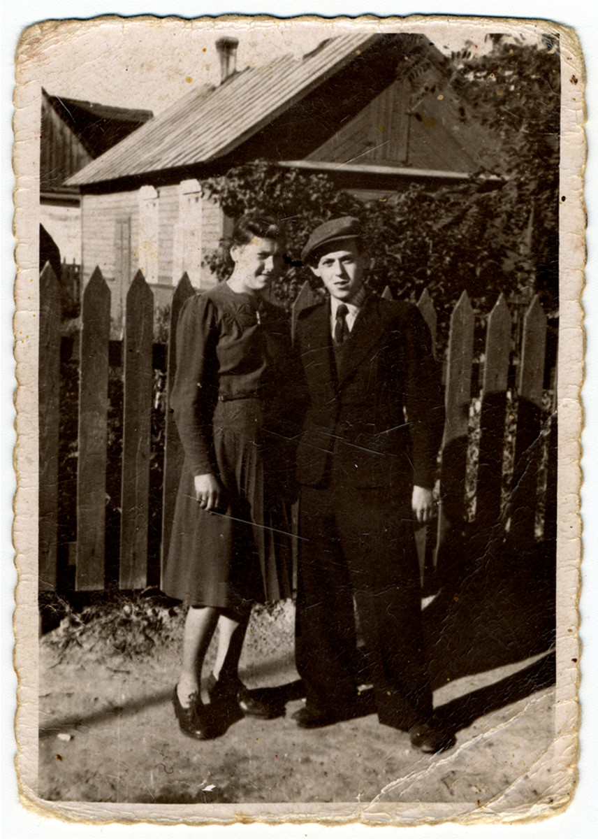 Portrait of a young couple standing by a fence [possibly in the Deblin ghetto].