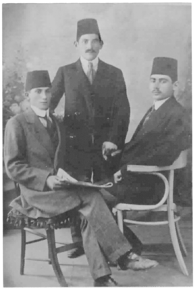 Studio portrait of three men wearing fezes.  Jules Hodak is seated on the left.