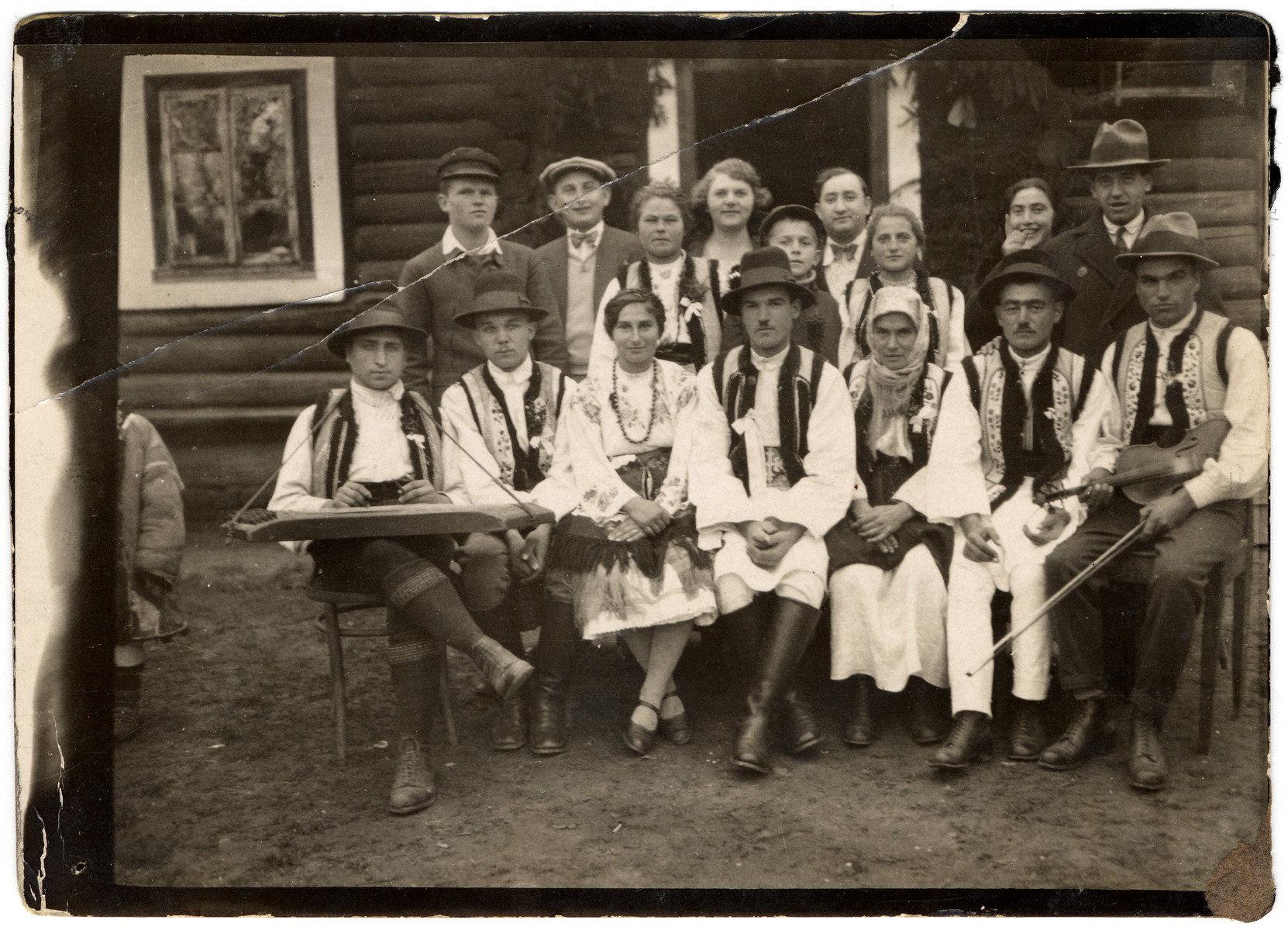 Members of the Lifschitz family pose with a group of Romanian peasants wearing embroidered vests that Avraham David Litschitz wove in his textile shop.  Pictured in the back row are Avraham David Lifschitz (second from left), Joseph Sperling (Avraham David's brother-in-law visiting from America, center) and Avraham David's sister and her husband, Esther and Mendel Mechlowitz (far right).
