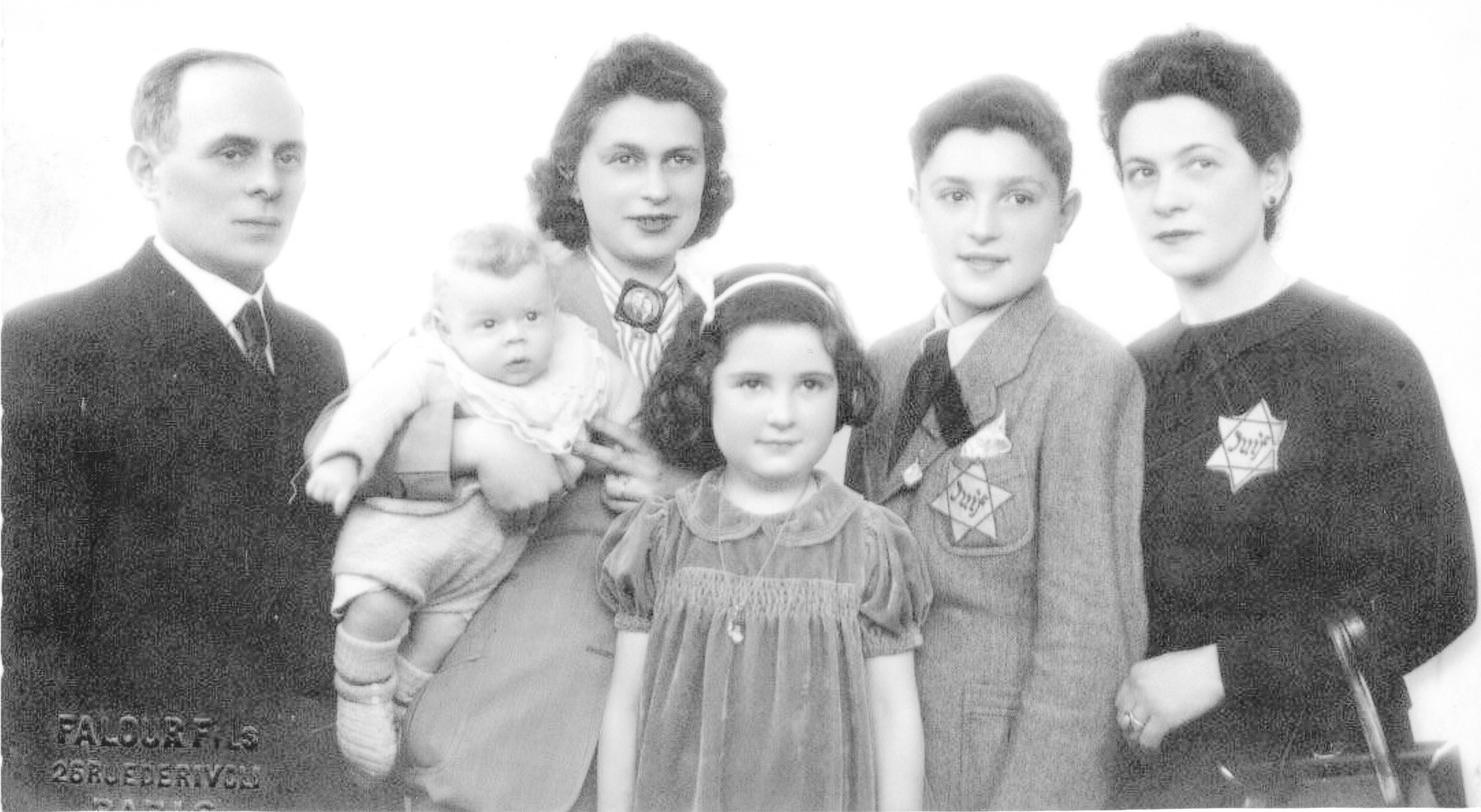 Portrait of a French Jewish family wearing Jewish stars.  From left to right are Victor Perelstein, Eva Perelstein Pelcholding her baby Jean-Claude, Giselle Rachlin, George Rachlin, and Cecile Perelstein Rachlin. (Cecile's husband died on the Maginot line during the invasion of France.)