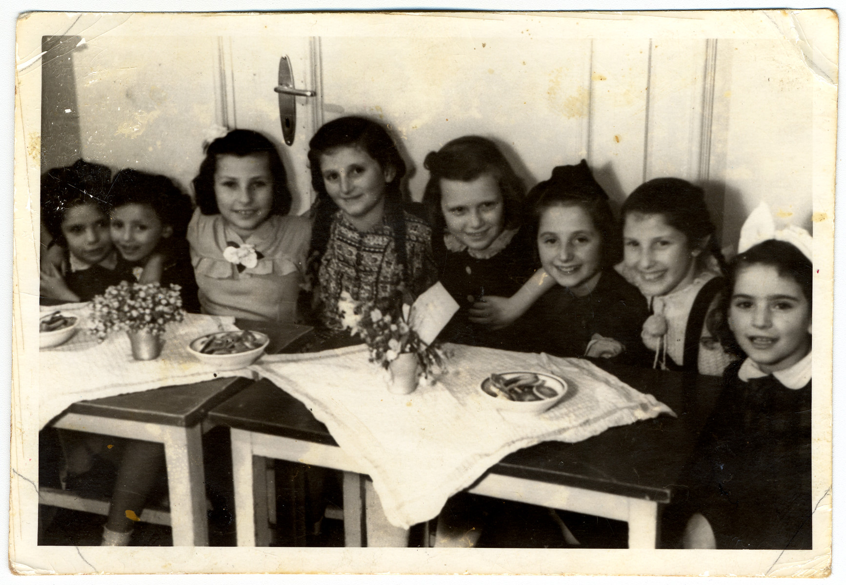 School girls sit by a table to celebrate their teacher's wedding in the Feldafing displaced person's camp.  Among those pictured are Miriam (second from left), Rutak Kron (third from left), Rifka Lischitz (fourth from left), Ada Rosenberg (fifth from left) and Leah (sixth from left).