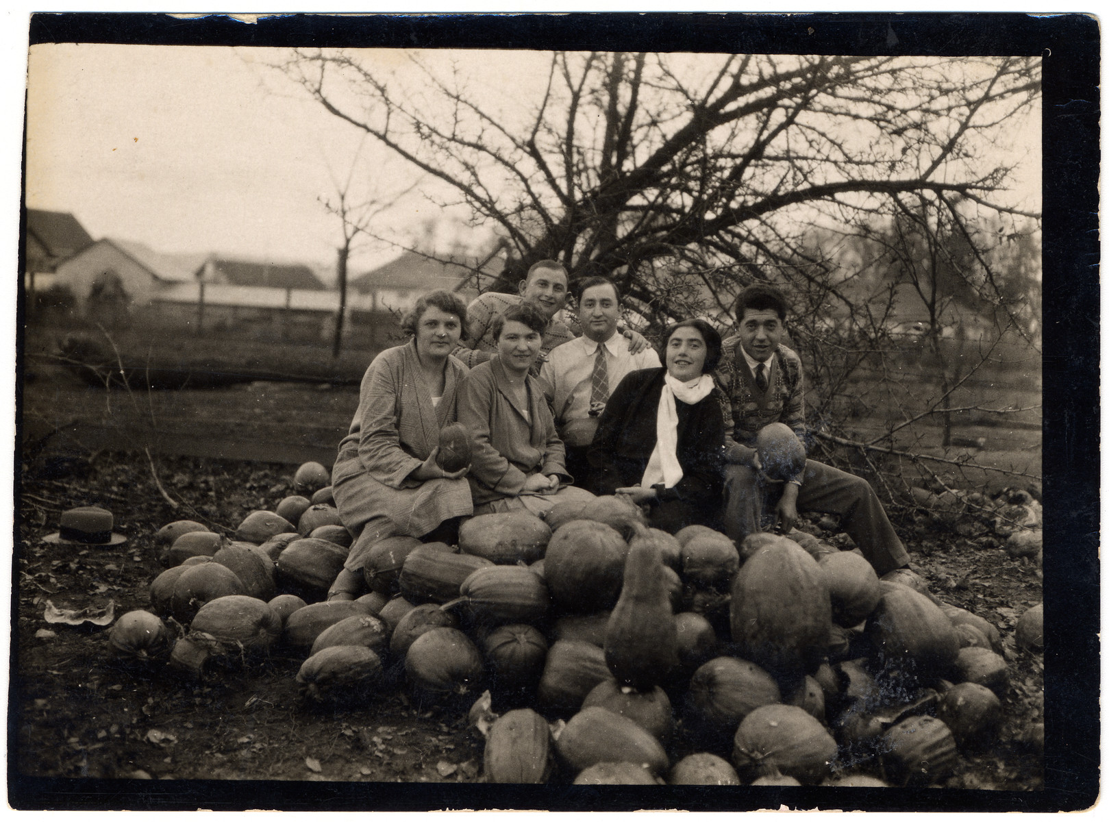 Members of the Lifschitz family pose in a pumpkin patch on the occasion of a visit from a relative from America.  The first two women on the left are unidentified.  Then viewed from left to right are Avraham David, his brother-in-law from America Joseph Sperling, Esther and Mendel Mechlowitz.