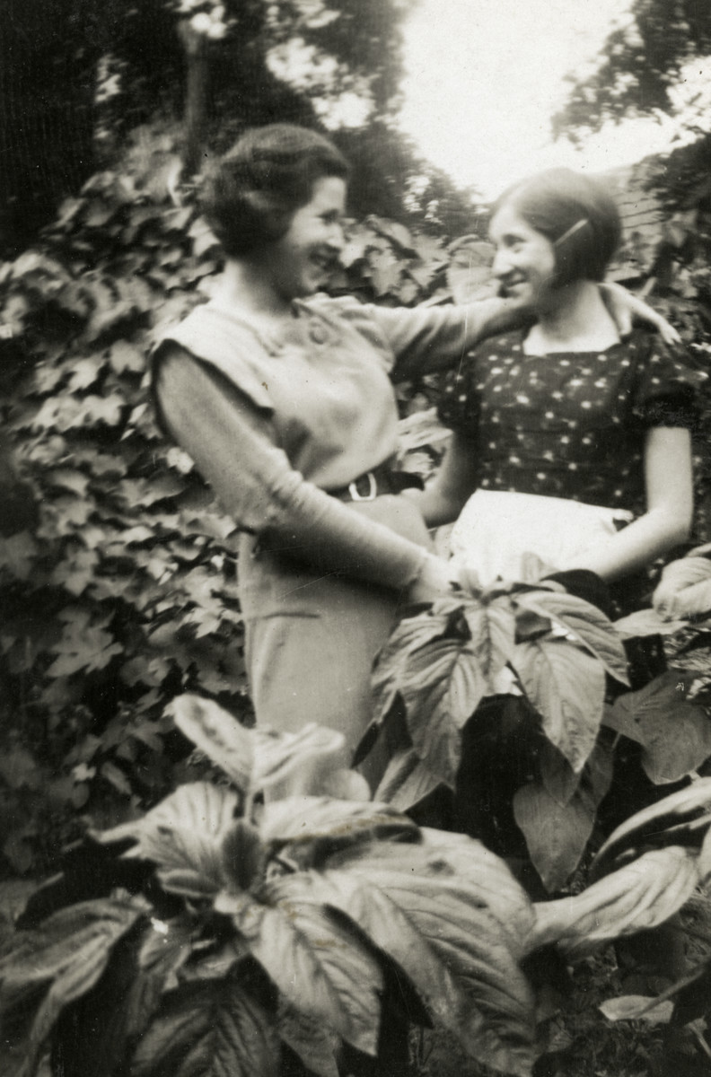 Sisters Magda and Yehudit Scharf pose in the garden of their home.