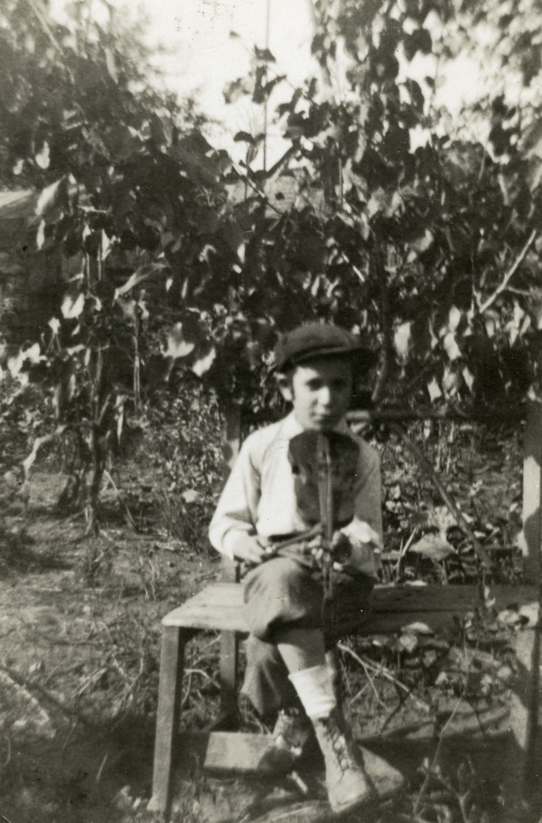Bondy Scharf sits in the garden of his home holding his violin.