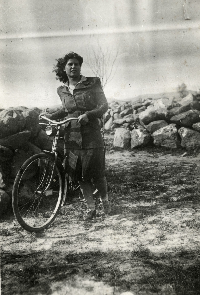 Esther Schaechter walks her bicycle through a field in wartime Hungary.