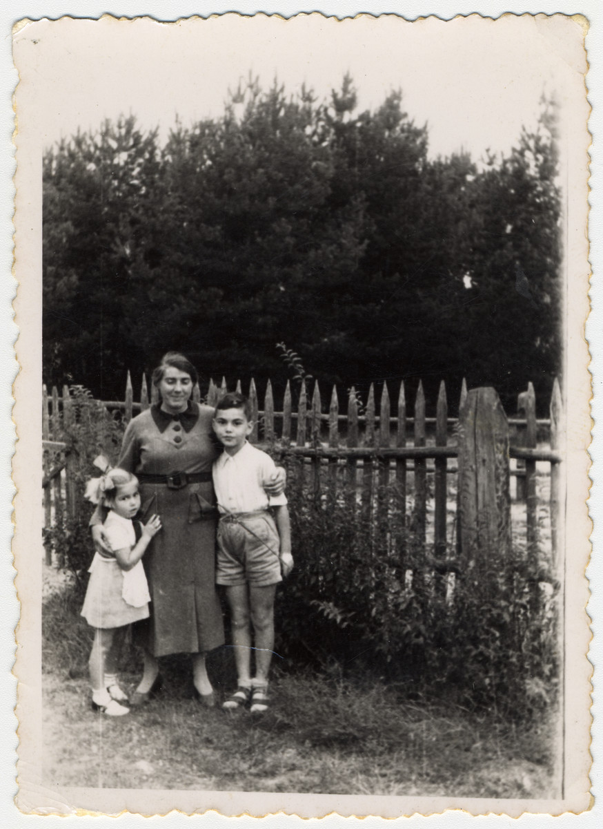 Julius and Bella Menn pose next to the their German governess, Maria Lipke, by a fence in a garden.