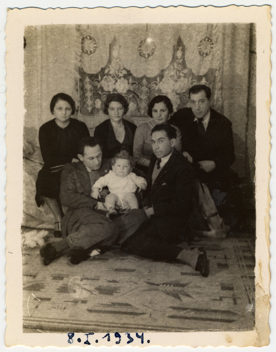 Group portrait of family and friends of the Litman family in prewar Krakow.  Pictured are Mrs. Kantor (left, top row), Isaac Litman, holding baby Halina, Olga Litman (Schreiber) behind. Luciek next to baby, Zalesch. The curtains in the background were made by Olga Litman.