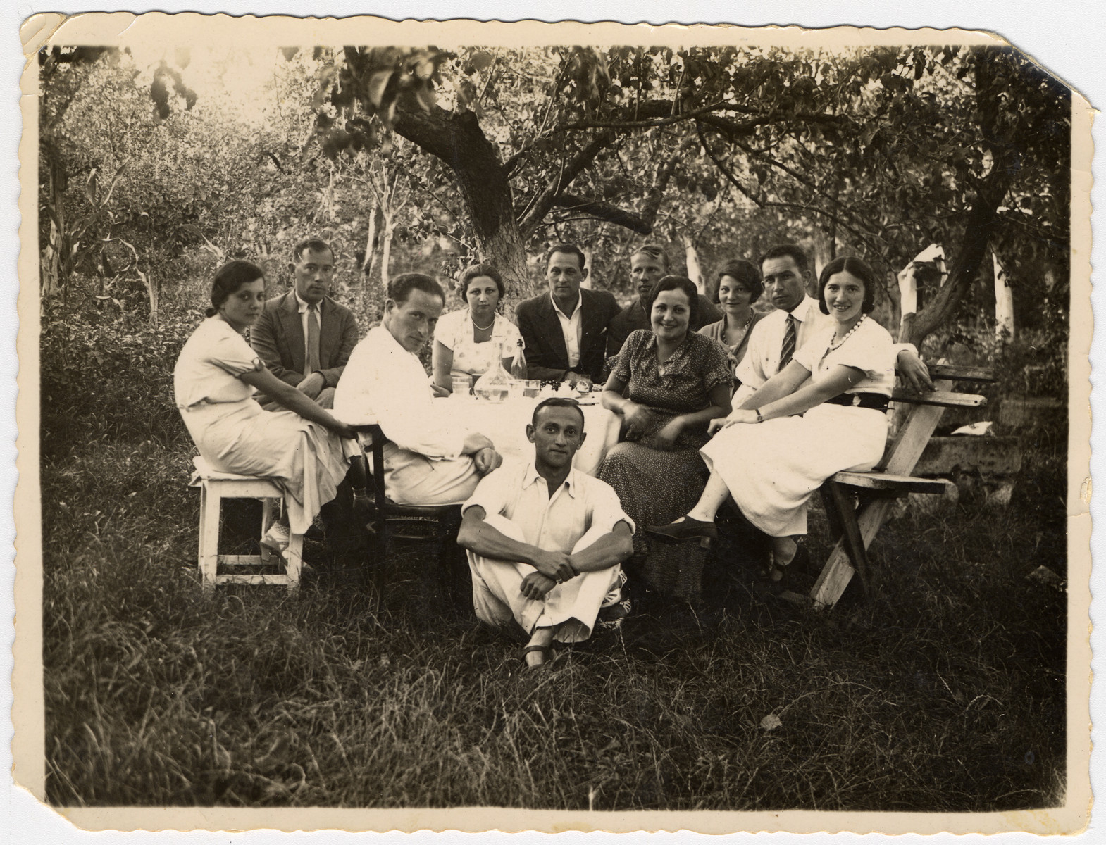 Prewar portrait of a group of family and friends sitting by a table outside.  Isaac Litman is pictured in the in dark jacket.  His wife Olga Litman is in the middle. On the front right is Lusiek who was in Judenrat in Zales and helped obtain false papers.