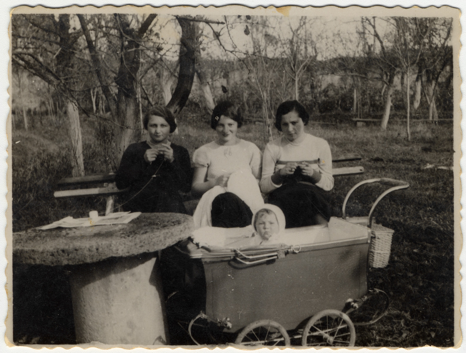 Olga Litman (middle) sits on a park bench and knits while watching her baby Halina sitting in a carriage.