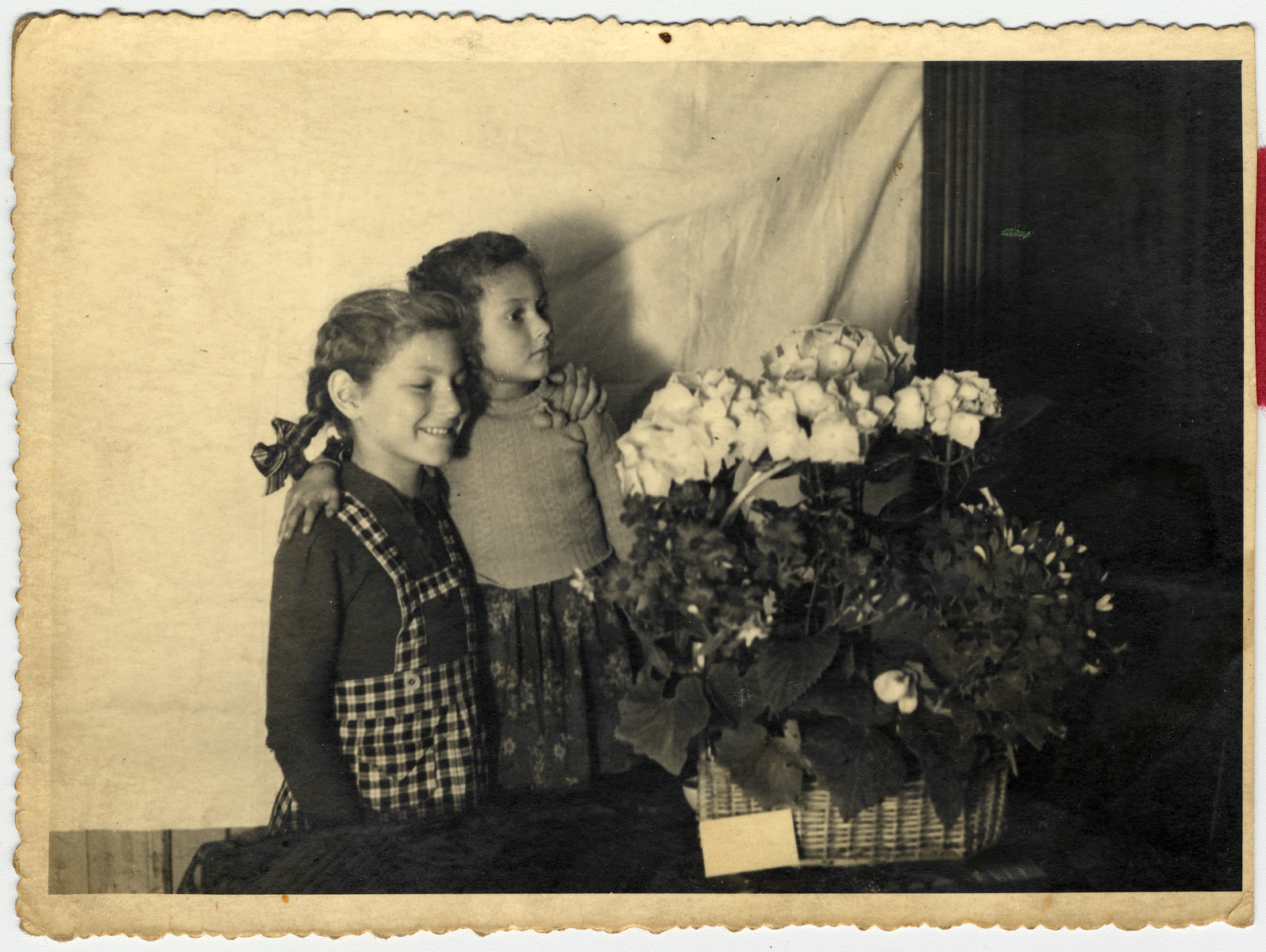 Sisters Halina  and Eva Litman pose next to a basket of flowers while in hiding in Jaroslaw.   Eva is standing on a chair so they appear to be the same height.