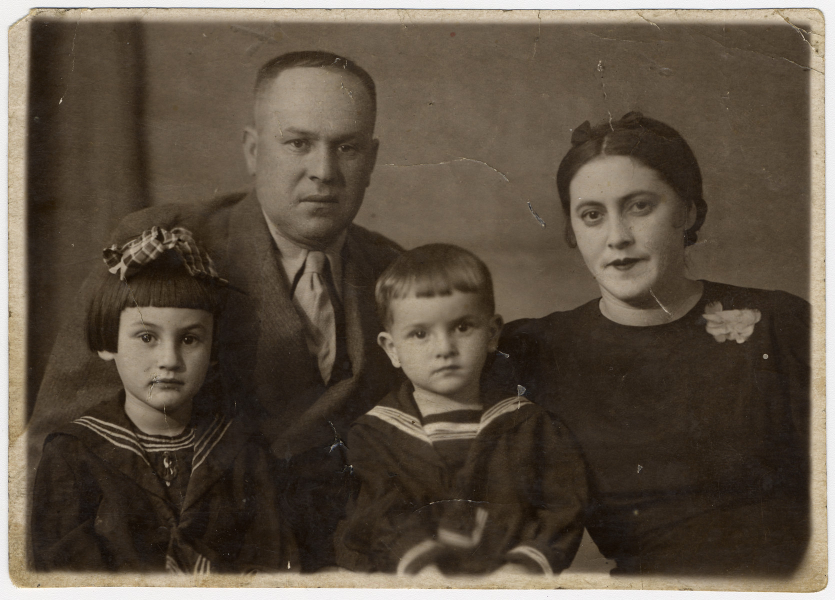 Studio portrait of Sonia (nee Ziegelman) and Pinchas Khanuk and their two children Bella and Izya.