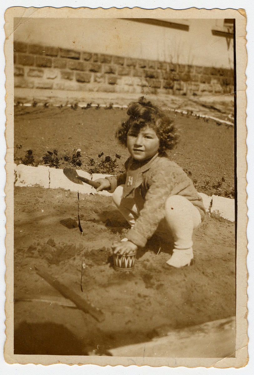Halina Litman digs in a garden, wearing a sweater knitted by her mother with the initial 'H'.