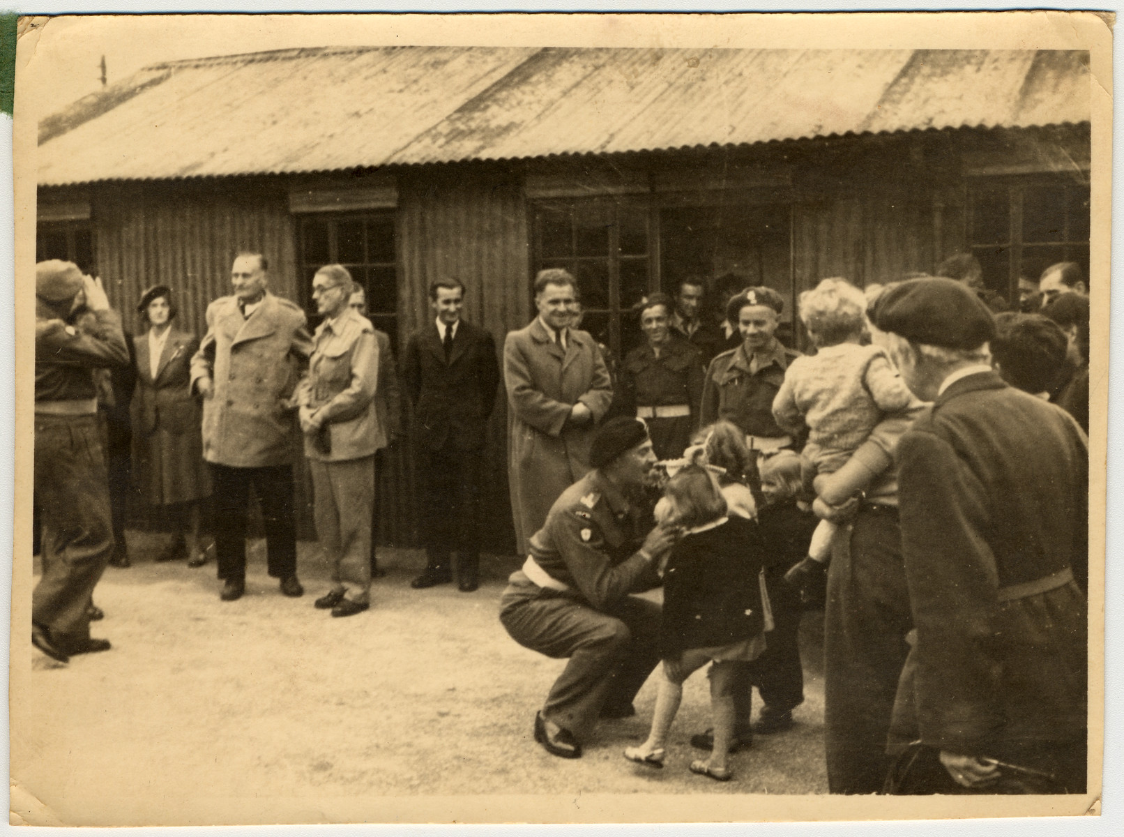 "Eva Litman is pictured, greeting General Wladyslaw Anders with flowers.  Original Caption Reads: ""Am sending you a picture from my stay in England""."