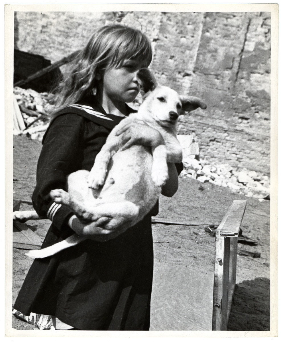 A Polish girl holding her dog in her arms views the destruction wrought by German air raids during the siege of Warsaw.