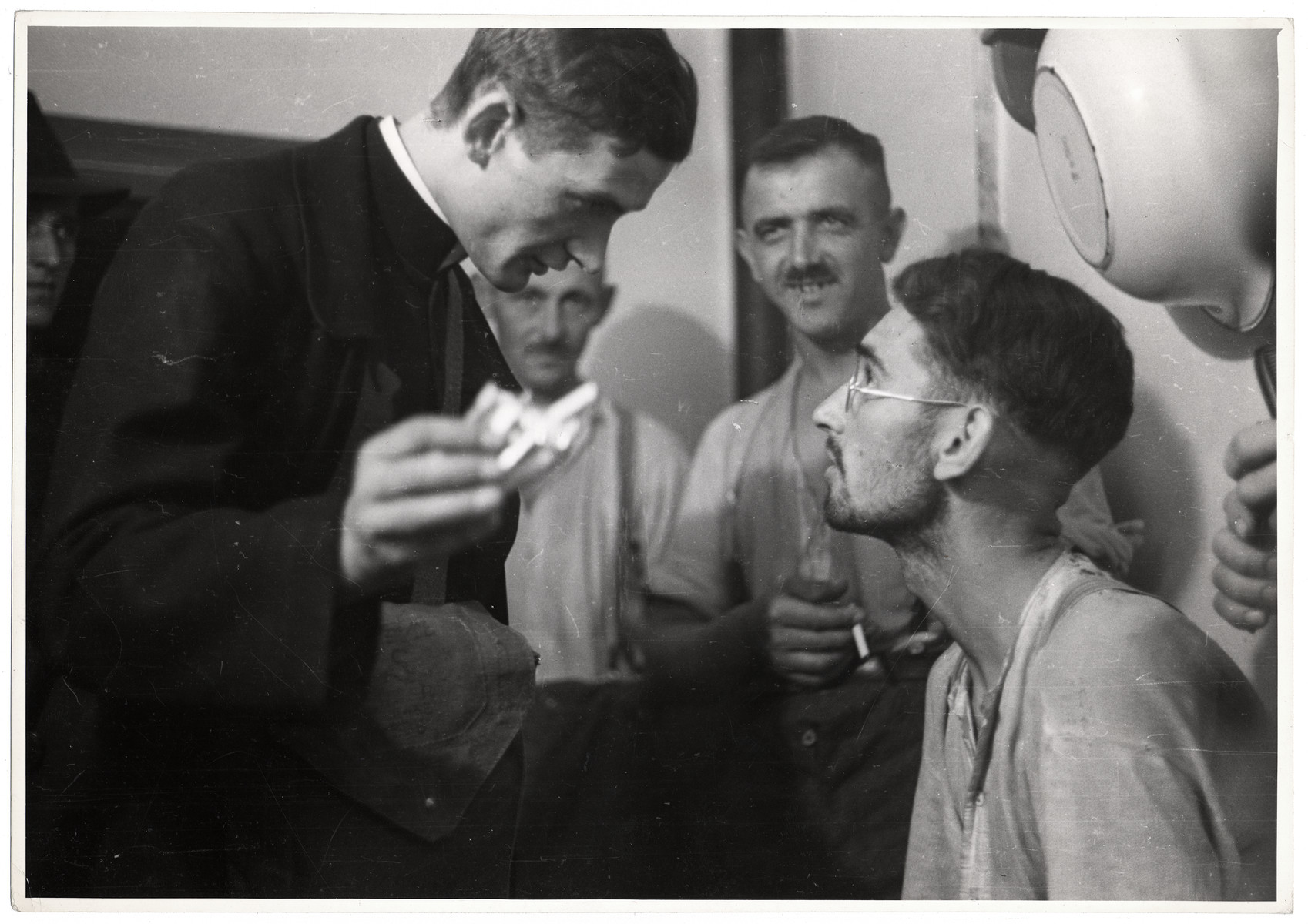 A Polish priest visits German POWs and offers them cigarettes.