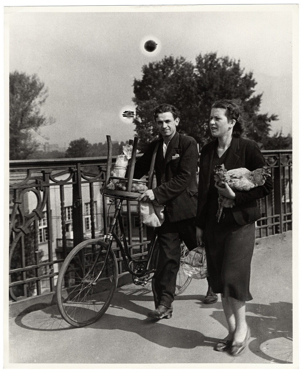 A young Polish couple walks through beseiged Warsaw with a chicken and chair.