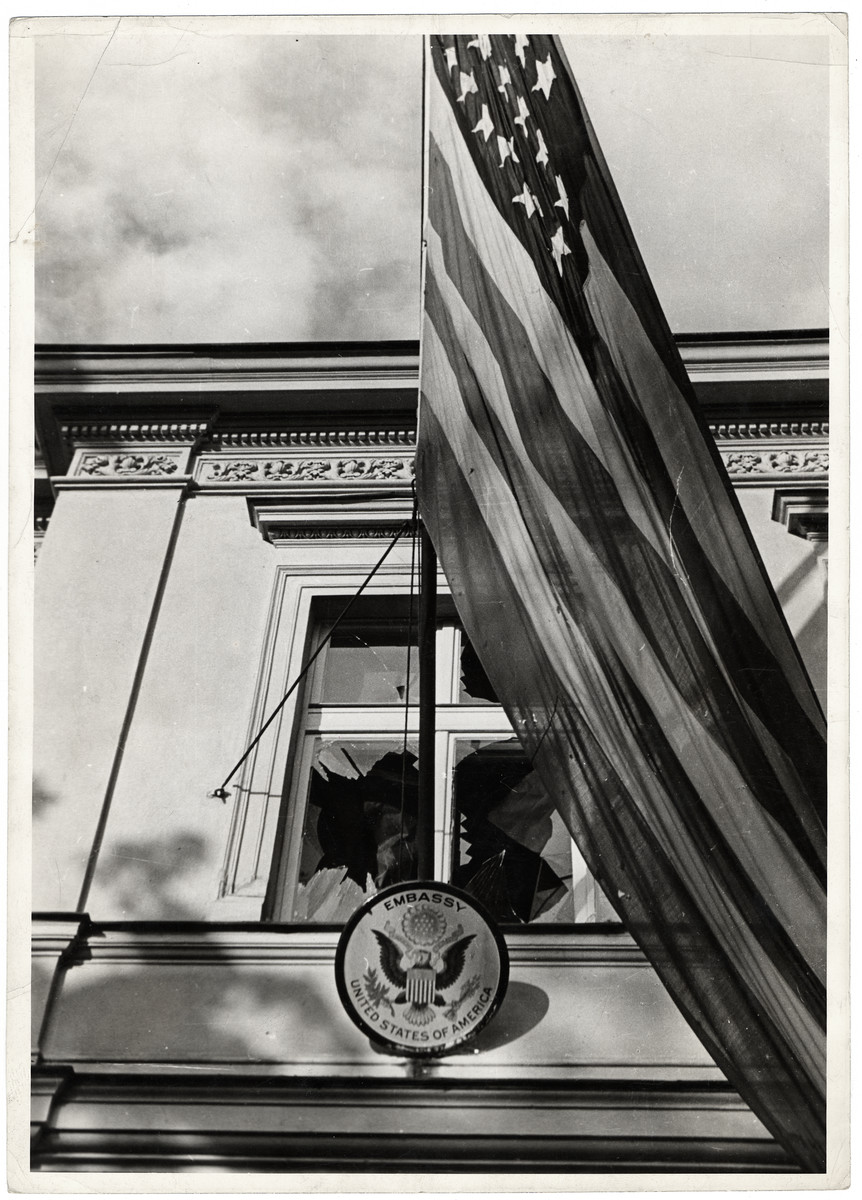 An American flag hangs outside the shattered window of the American embassy in Warsaw during the siege of the capital.