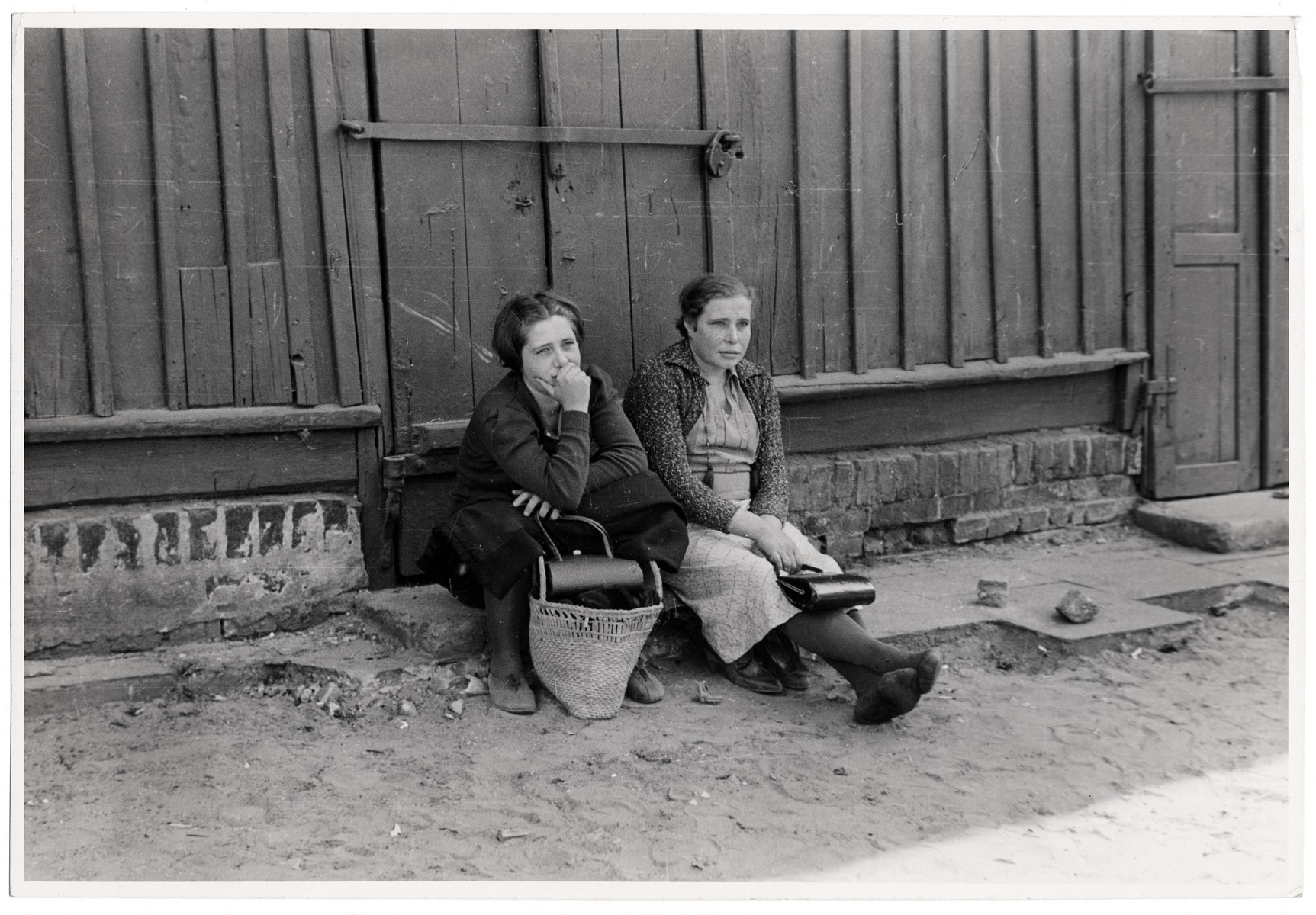 Two Polish women sit on a stone step in besieged Warsaw.